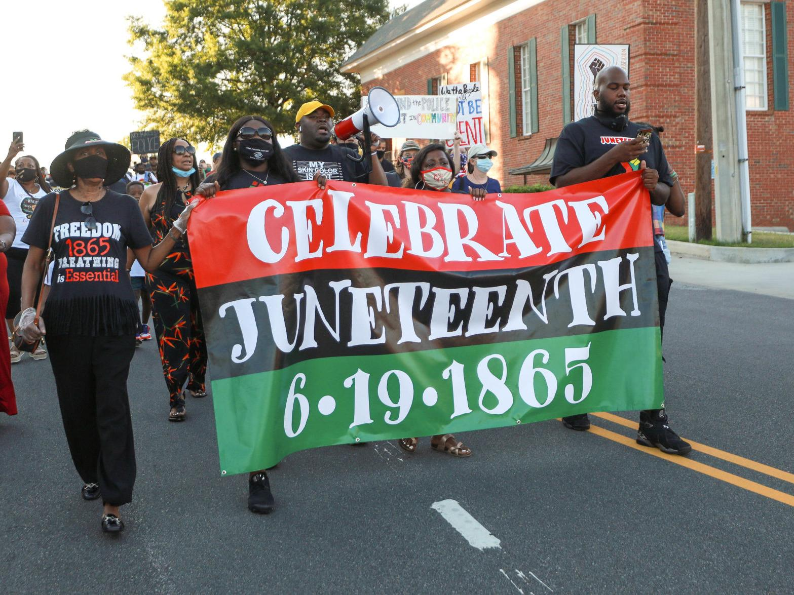 People marching while holding a Juneteenth banner