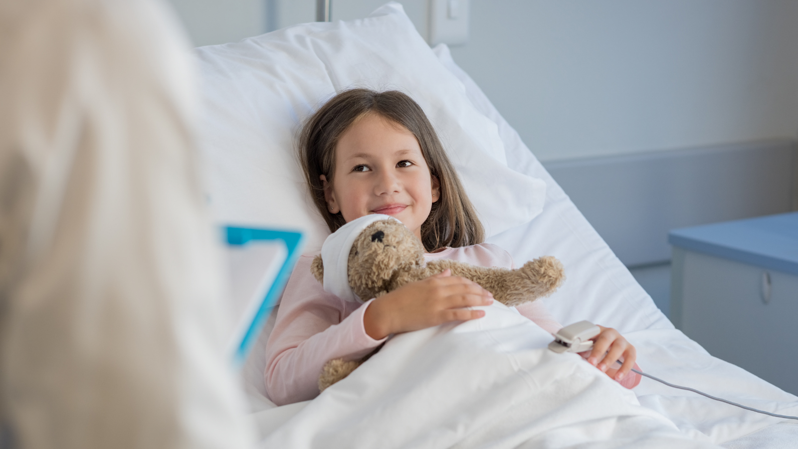 Child in hospital bed holding a teddy bear